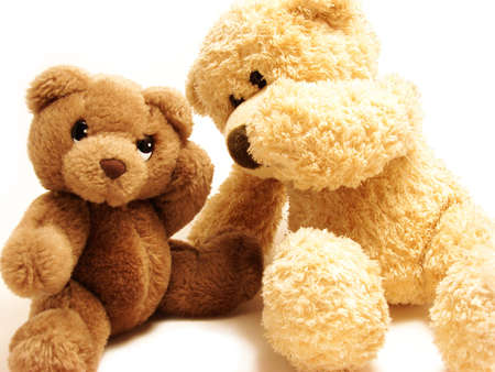 soft toy:   teddy-bear whispering secrets to the other one                                Stock Photo