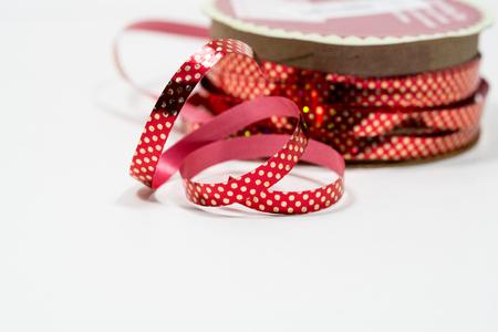 ribbon, a spool of ribbon unraveling, christmas ribbon, red polka dot ribbon