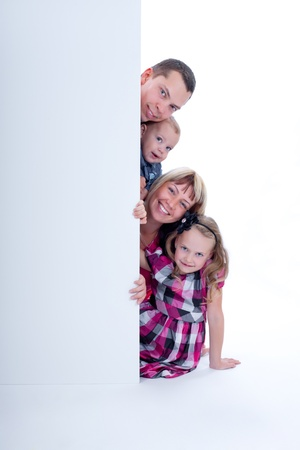 Happy smiling family looking out from behind the wall Stock Photo - 15904127