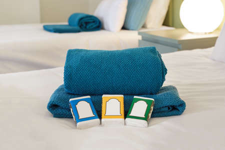 Hotel room bed with towels and soap bars with customizable labels Stock Photo