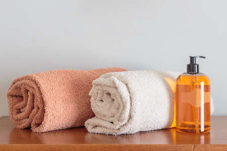 Shampoo bottle and towels on counter. Table top and copy space Stock Photo