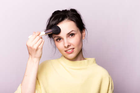 attractive woman in a yellow sweater does makeup with a brush Foto de archivo