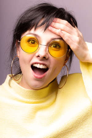 happy woman with bangs, yellow clothes, gray background 版權商用圖片