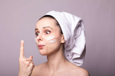 girl with a white towel on her head and cream on her face