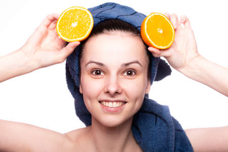 funny woman after shower in a towel on her head holds an orange, skin care, vitamins, fruits