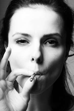 brunette woman smokes a cigarette Archivio Fotografico