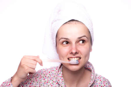 woman in a towel on her head brushes her teeth