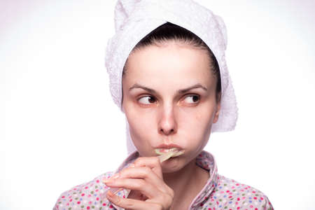 beautiful woman in a towel on her head brushes her teeth with a toothbrush, toothpaste flows on the brush, light background