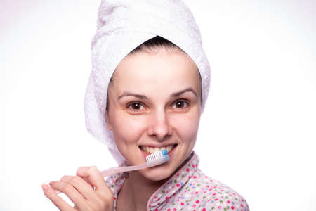 woman in pajamas brushes her teeth after a shower, close-up portrait