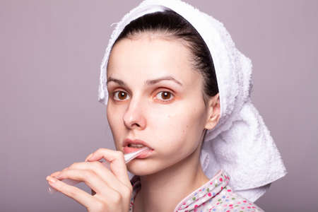 woman in pajamas and a towel on her head brushes her teeth with a toothbrush, closeup portrait