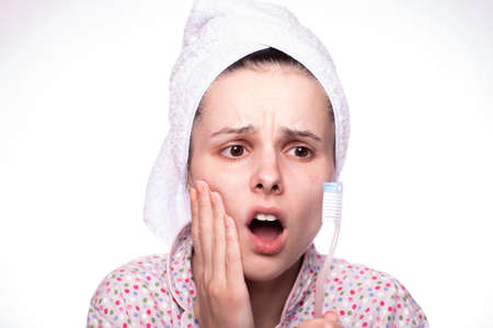 beautiful woman in a towel on her head is in pain when brushing her teeth, dentistry