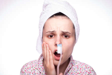 beautiful young woman in a towel on her head brushes her teeth and has a toothache, light background