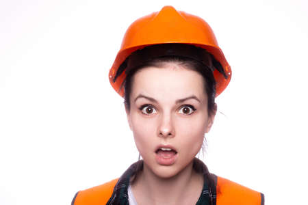 beautiful woman in an orange helmet and vest, light background Standard-Bild