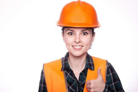 woman in an orange helmet and vest, light background