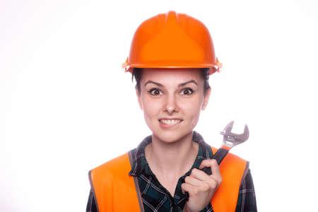 female plumber in orange helmet holds tool, hardware store Standard-Bild