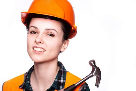 attractive woman builder in a protective helmet and an orange vest with a hammer in his hands, a hardware store, husband for an hour Standard-Bild