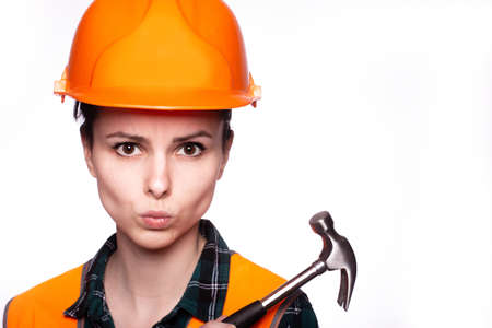 attractive woman builder in a protective helmet and an orange vest with a hammer in his hands, a hardware store Standard-Bild