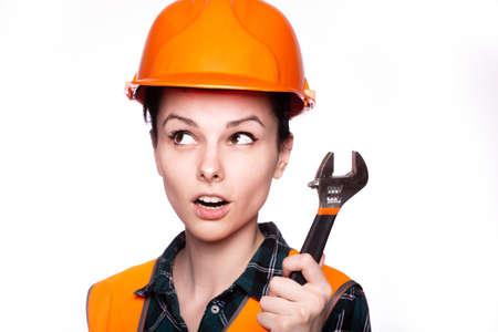 female plumber in an orange helmet with a wrench Standard-Bild