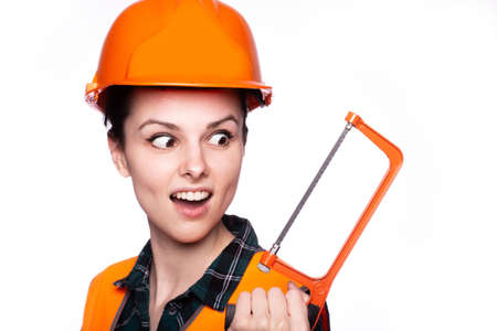 Cute woman builder in a protective helmet and orange vest with a saw in his hands, light background