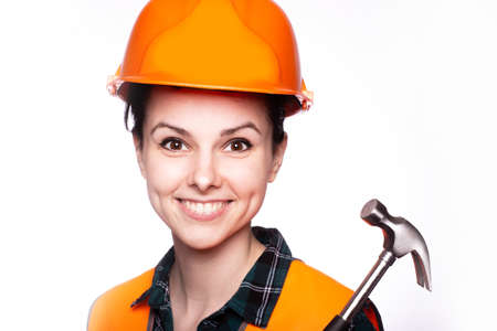 woman in an orange hard hat with a hammer in her hands Banco de Imagens