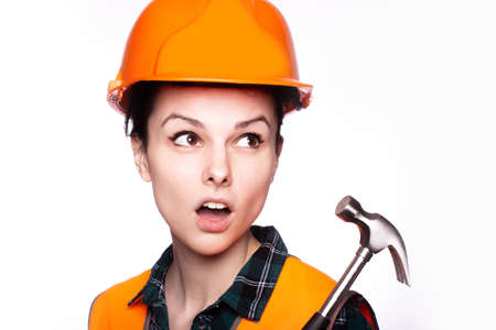 woman in an orange helmet and a yolk, with a hammer in her hands