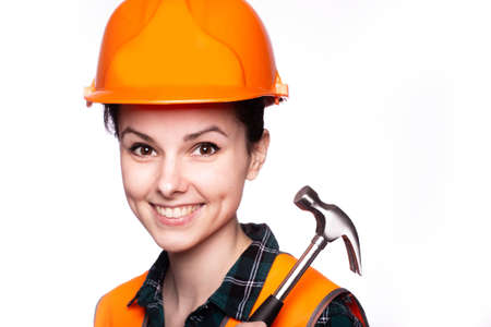 beautiful young girl worker in a helmet holds a hammer in his hand, construction site Banco de Imagens