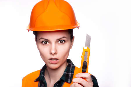 beautiful woman worker in a construction helmet and orange vest holding a construction knife