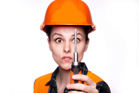 beautiful woman worker in a construction helmet and orange vest with a screwdriver in her hands