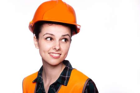 beautiful woman worker in a construction helmet and orange vest