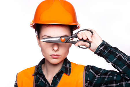 female plumber in a construction helmet and vest with a tool in her hands