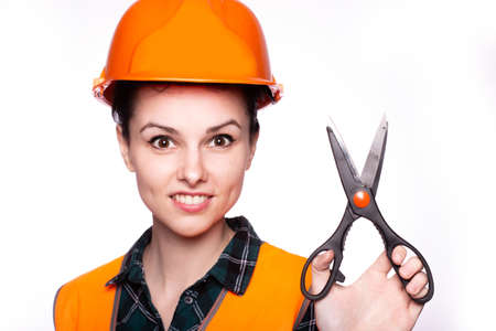 beautiful woman builder in a protective helmet and orange vest with scissors in her hands, light background