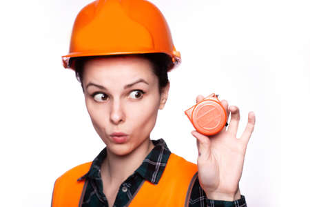 beautiful young woman architect in helmet holds tool in hand Standard-Bild