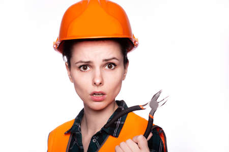 builder woman in uniform with tool in hand, light background