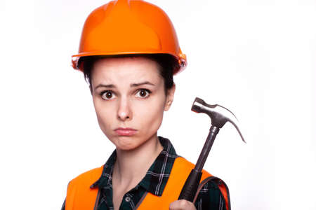 beautiful young woman electrician in a helmet holds a tool in her hand