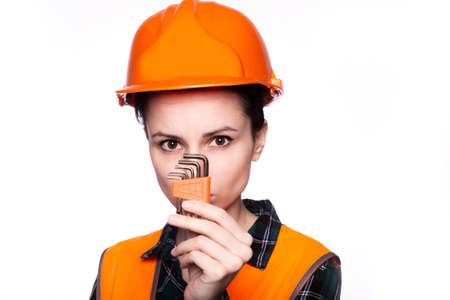 beautiful young woman a plumber in a helmet holds a tool in her hand Standard-Bild
