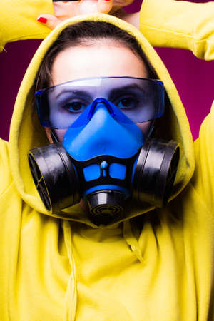 woman in respirator, goggles, green hoodie, pink background