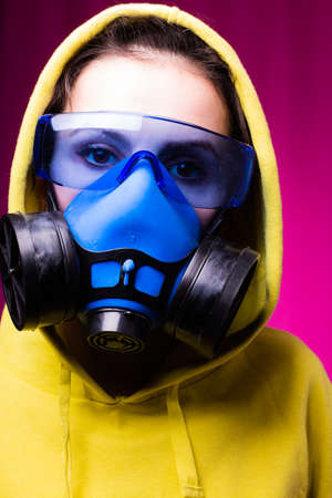 woman in blue respirator mask, goggles and green hoodie, pink studio background