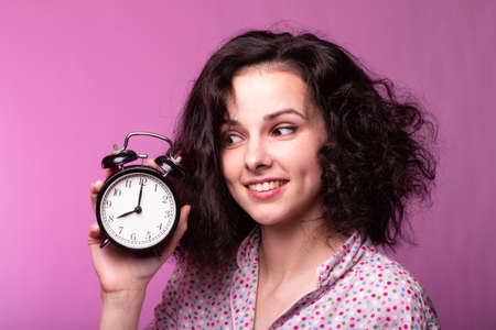 curly woman in pajamas with an alarm clock in her hands, pink background