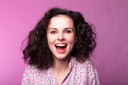beautiful curly emotional woman in the morning in pajamas, pink background
