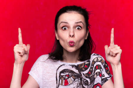 woman in a white T-shirt on a red background, emotional portrait