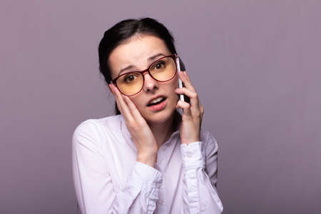 female manager in a white shirt is emotionally talking on the phone, gray background