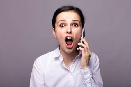 cute businesswoman in a white shirt is emotionally talking on the phone, gray background Reklamní fotografie