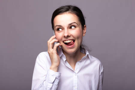 cute businesswoman in a white shirt is emotionally talking on the phone, gray background