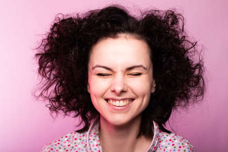 funny curly girl in a nightgown, pink background
