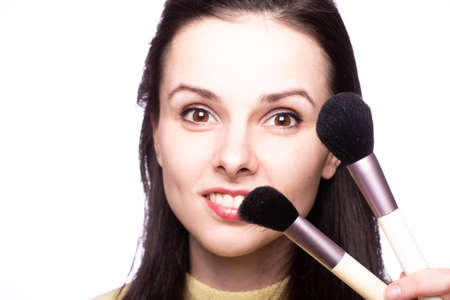 attractive girl does makeup, makeup brush Imagens