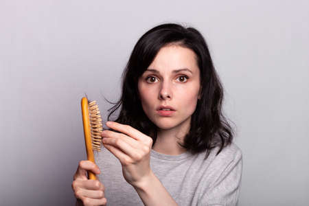 Woman holding the hair brush. The problem of hair loss.