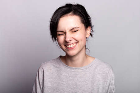 lovely girl in a gray t-shirt on a gray background smiles