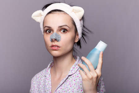 funny woman in a long-eared hair band holding a cosmetic bottle with a face tonic, a plaster from black dots on the nose, treatment of problem skin, gray studio background