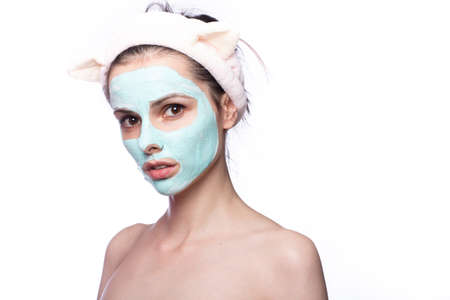 woman with blue clay face mask, funny eared hair band, home face skin care Stock fotó