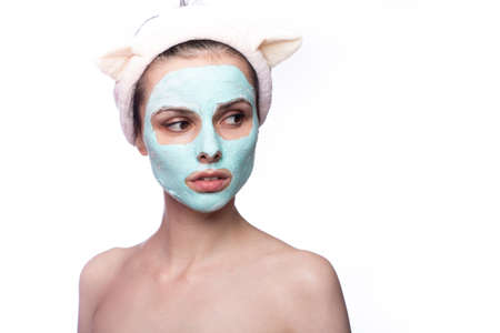 woman with blue clay face mask, funny eared hair band, home face skin care Standard-Bild
